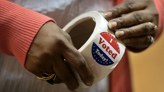 A poll worker peels off stickers for voter at the Geeter Middle School polling location Tuesday morning in Whitehaven.