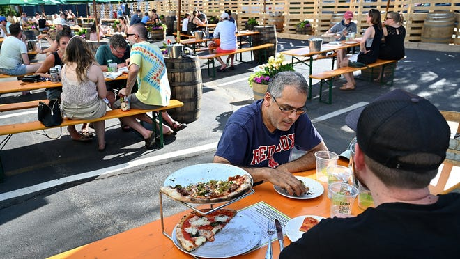 Fadel Ghozayel of Framingham and Chris Berg of Woburn enjoy drinks and a meal at Jack's Abby in Framingham on Thursday, June 18.