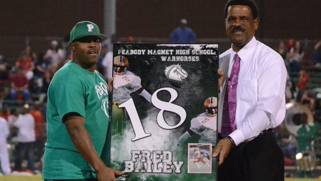 Former Peabody all-state receiver Fred Bailey (left) is presented with a framed poster by Peabody athletics director Charles Smith during halftime of Friday night's football game. Bailey, a former standout at Southern who played in the CFL, had his No. 18 jersey retired by the school.