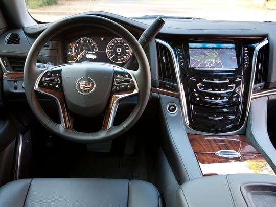The 2015 Cadillac Escalade is shown with Jet Black interior with Santos Palisander wood accents.