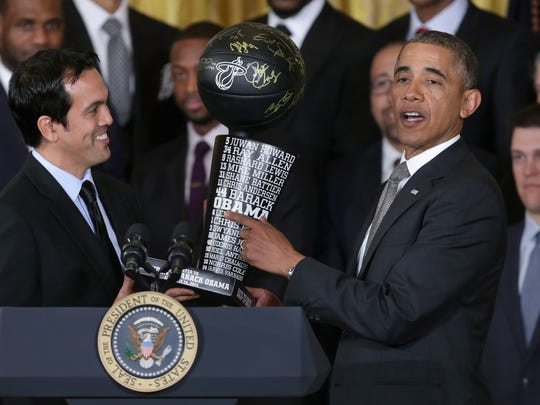 President Barack Obama points to his name on a commemorative trophy given to him from the Heat from Erik Spoelstra during a ceremony honoring the 2013 NBA champions.
