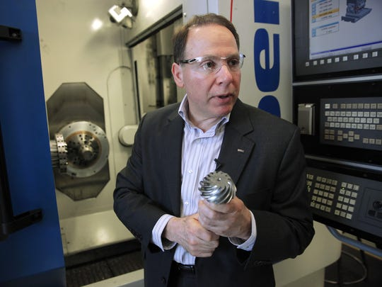 John J. Perrotti, President and Chief Executive Officer of Gleason Works explains the operation of a gear cutting machine.