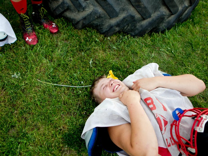Senoir Kyle Kunze jokes with teammates during a break in football practice at Abbotsford High School, Thursday, Aug. 7, 2014.