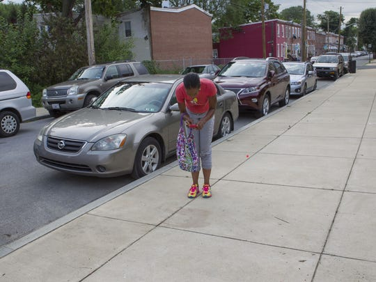 A woman who identified herself as the cousin of man shot to death stops to take a picture of the blood spot on the sidewalk Thursday morning in the 100 block of 22nd St. in Wilmington.