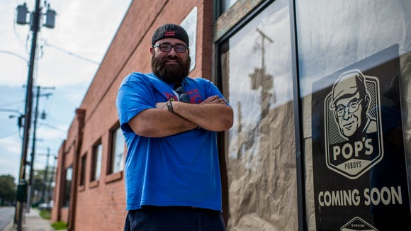 Collin Cormier, owner and chef of Pop's Po-Boys, poses for a photograph next to a restaurant sign at the building in downtown Lafayette, La., Monday, March 16, 2015. Cormier hopes to open the restaurant in April 2015.