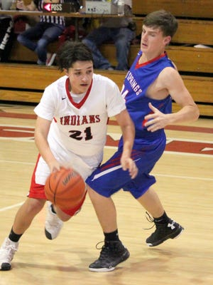 Cobre's Glen Montoya attempts to drive around a Hot Springs defender during action Monday night. He finished with six points on the night, sinking two shots from beyond the arc.