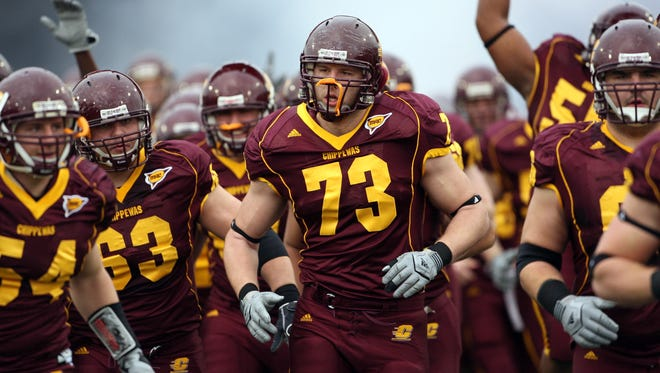 Central Michigan offensive lineman Jake Olson (73) leads his team onto the field to take on Northern Illinois at Kelly Short Stadium.