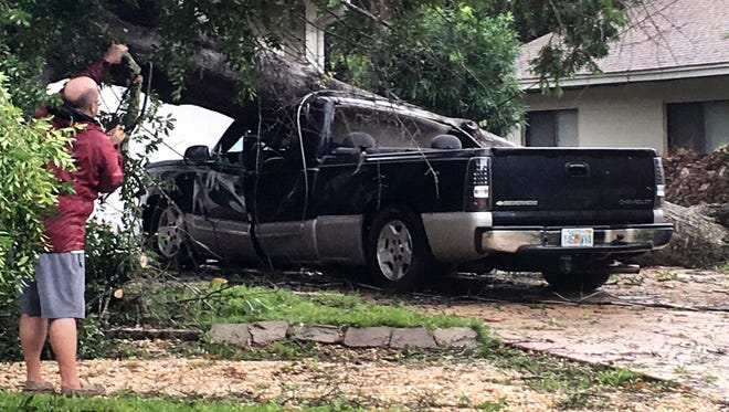 An unidentified man looks at a truck that was crushed by a falling tree in Fort Walton Beach, Florida on Wednesday, June 21, 2017. This Florida panhandle community was hit by a wave of severe weather Wednesday morning as Tropical Storm Cindy churns through the Gulf of Mexico.