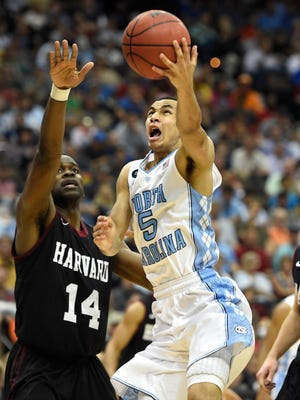 North Carolina Tar Heels guard Marcus Paige (5) drives to the basket against Harvard Crimson forward Steve Moundou-Missi in the second round of the 2015 NCAA Tournament