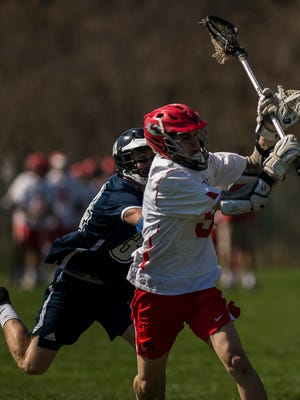 CVU's #5 Jake Schaefer gets a shot off past Burlington's #34 Ryan Mitchell during their boy's lacrosse game in Hinesburg on Tuesday, May 8, 2018. CVU won, 12-4.