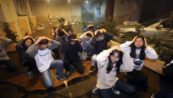 Students participate in a training program to take shelter from an earthquake at a school in Seoul, South Korea, Nov. 16, 2017.
