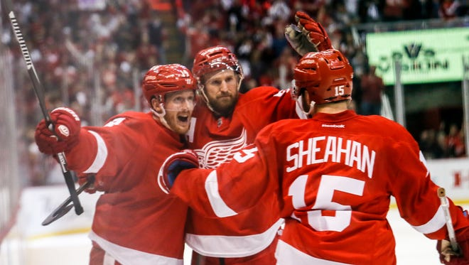Red Wings forward Gustav Nyquist, left, celebrates his goal with teammates Niklas Kronwall and Riley Sheahan during the second period of Game 4 Tuesday at Joe Louis Arena.