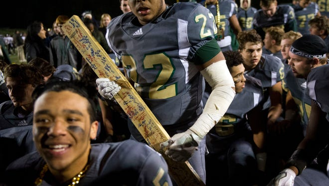 Knoxville Catholic's Joe Fluker carries a 2x4 after their 44-14 win over Fulton on Friday, November 10, 2017.
