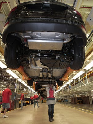 Breanna Tunstall works on the brake lines of the 2012 Ford Focus at the Ford Motor Co. Michigan Assembly Plant in Wayne, Michigan, on March 17, 2011.