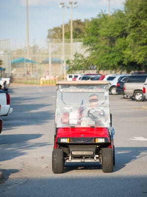 A golf cart makes its way through the parking lot at Shoreline Park in Gulf Breeze on Tuesday, April 10, 2018.