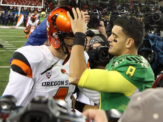 Marcus Mariota pats Sean Mannion on the helmet after the Ducks blow out the Beavers 47-19 in the annual Civil War college football battle between Oregon and Oregon State at Reser Stadium in Corvallis.