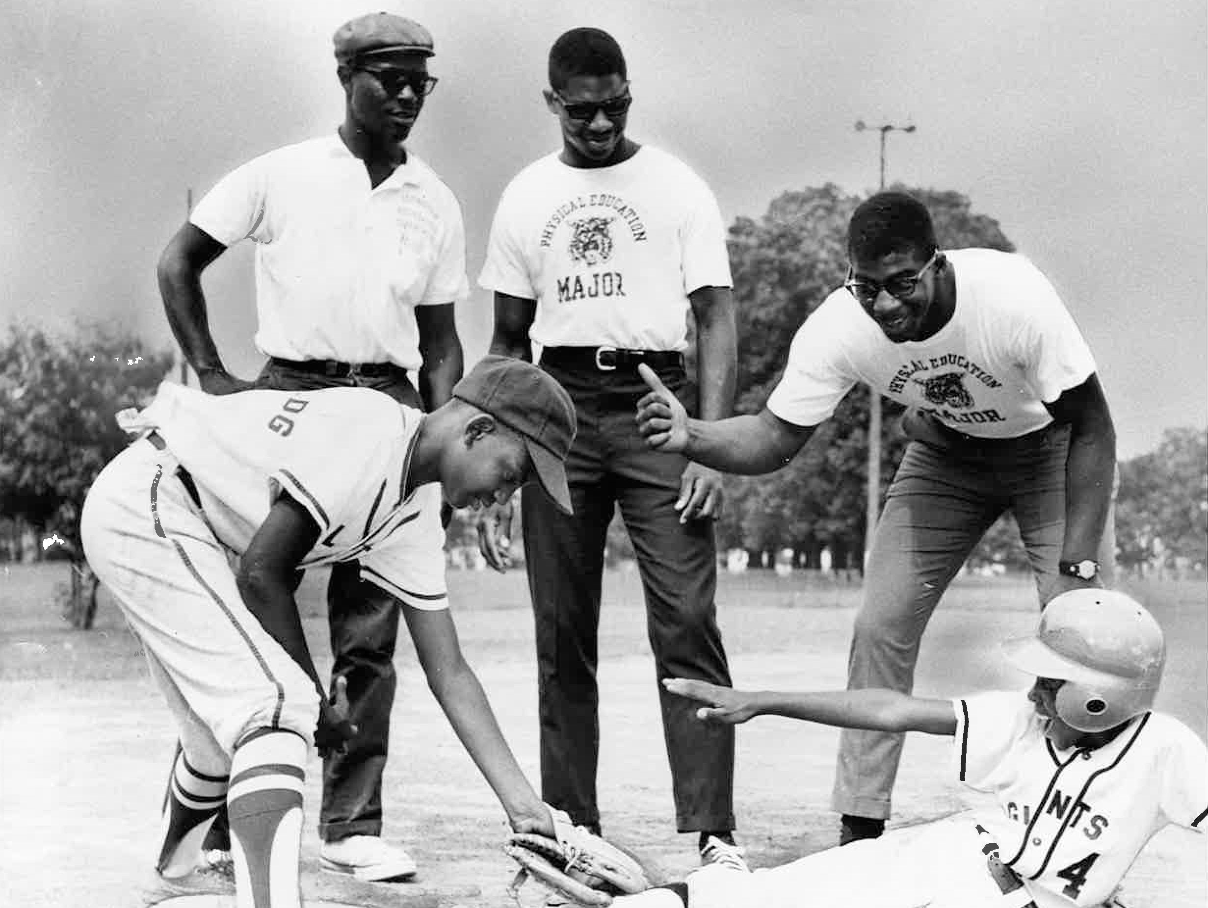Nate Northington, center, and Greg Page, at right giving the out signal, look on during a photo shoot in July 1967. Northington and Page went on to become the University of Kentucky's first African-American varsity football players that fall. Eric Johnson is seen tagging out Gay Martin during a Little Mite practice at Lexington's Douglass Park. Watching at left is Sam Adams of the city's recreation department.