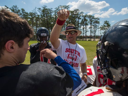 Brian Conn, the new head football coach at South Fort Myers High School, discusses a drill with during a team practice Tuesday (5/16/17) afternoon.