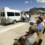 Glacier Park visitors wait for the shuttle at Logan Pass.