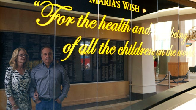"""John and Brenda Fareri are reflected on the wall that has their daughter Maria's wish at Maria Fareri Children's Hospital, July 29, 2014, in Valhalla, N.Y. Their story has been made into a new movie, """"Louder Than Words,"""" which stars David Duchovny and Hope Davis. Their daughter, Maria, died of rabies and the family worked to create the children's hospital in her name."""