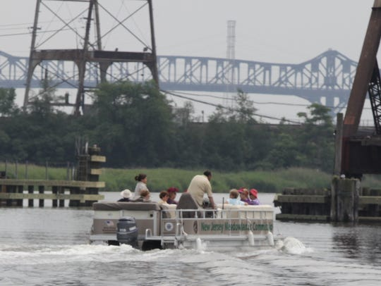 A pontoon boat navigates the Hackensack River in the