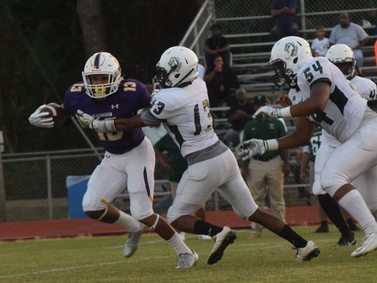 Alexandria Senior High School's Michael Orphey (13, left) gets past Peabody Magnet High School defenders Travion Brass (13, center) and Detetrius Lotts (54, far right) Friday, Sept. 15, 2017. Orphey was named to the LSWA Class 5A first team by sportswriters across the state.