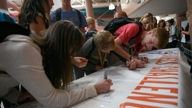 """Snow Canyon High School students sign their names to a poster in order to declare their intent to accept Rachel's Challenge in 2013. Rachel's Challenge's mission is to combat bullying and crate a """"culture of kindness"""" through the story of Scott's life and her writings. Rachel Joy Scott was one of the Columbine High School students killed in 1999."""