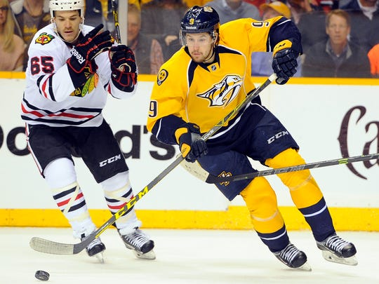 Predators center Filip Forsberg (9) skates with the puck past Blackhawks center Andrew Shaw (65).