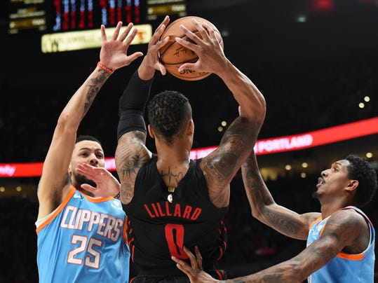 Los Angeles Clippers guard Austin Rivers, left, and Los Angeles Clippers guard Lou Williams, right, trap Portland Trail Blazers guard Damian Lillard, center, during the second half of an NBA basketball game in Portland, Ore., on Friday, March 30, 2018. The Blazers won 105-96. (AP Photo/Steve Dykes)