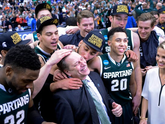 The Michigan State Spartans celebrates with head coach Tom Izzo after the game against the Louisville Cardinals in the finals of the east regional of the 2015 NCAA tournament at Carrier Dome.