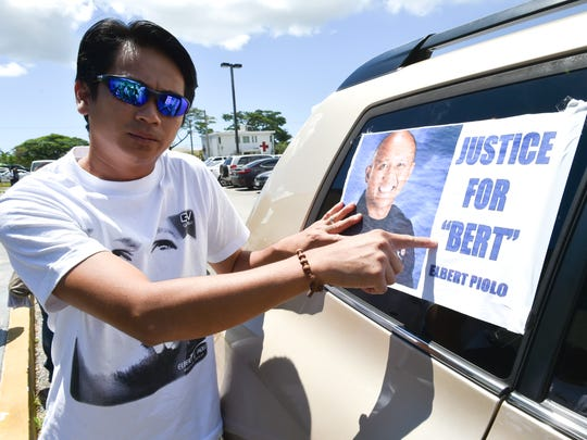 "Edison Piolo points to a poster expressing the family's desire in the case against Guam Police Department Officer Mark Torre Jr. just after an arraignment hearing for the defendant at the Superior Court of Guam on Wednesday, July 29. Torre pleaded not guilty to first-degree murder and other charges in the shooting death of Sgt. Elbert Piolo. ""All we want is justice for my brother. Basically, just that,"" Edison Piolo said after the hearing."
