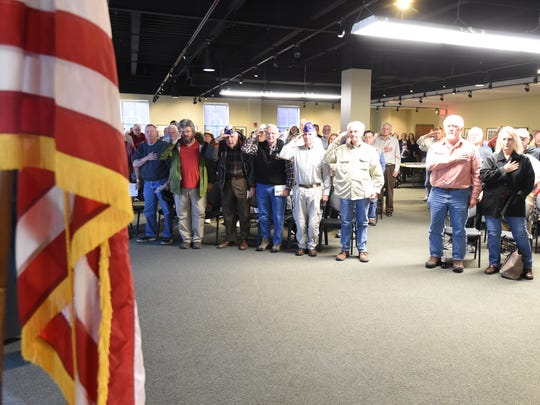 A standing-room only crowd of veterans recite the Pledge of Allegiance Friday, Feb. 19, 2016 during a town hall meeting at ASUMH. The meeting was held to inform veterans about the arrival of a new clinic to be overseen by a Virginia-based company, STG International.