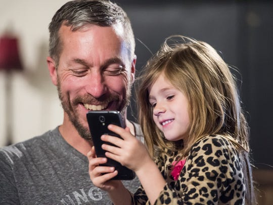 Chuck Messersmith holds five-year-old Natalie Potter as she plays with his cell phone on Wednesday, April 25, 2018. Messersmith is the owner of the Bourbon Bar and Grill and related properties and has been helping out Peggy Potter and her children since they were displaced by a house fire in late April.