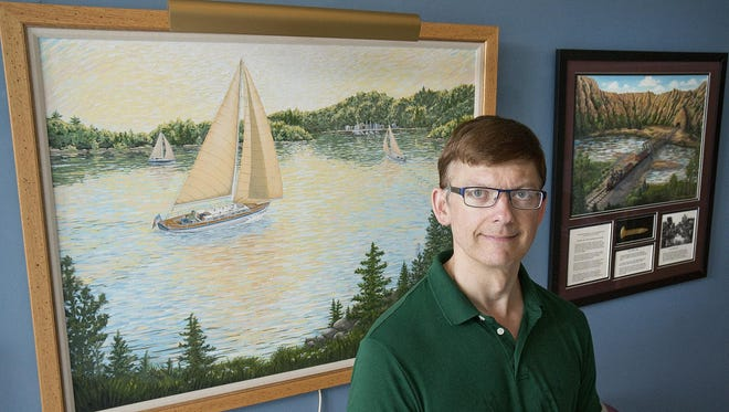 """Ross W. Anderson with an acrylic painting, """"Heading for Harbor."""""""