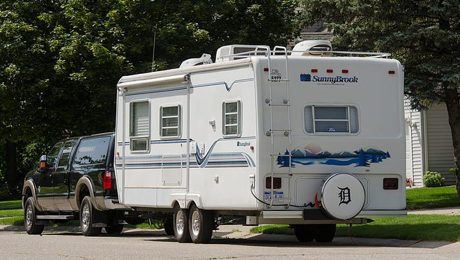 A recreational vehicle sits along the side of the road Tuesday in the Lake Pointe subdivision in Plymouth Township.