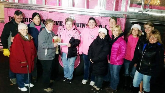 Members of Pink Heals accept a donation from PK's Beans N' Cream in Manitowoc.