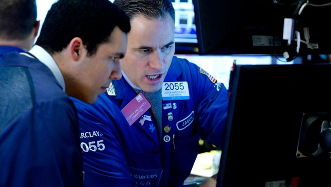 Traders work on the floor of the New York Stock Exchange (NYSE) at the start of the trading day in New York.