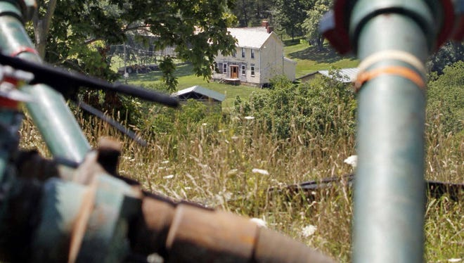 A farmhouse framed by pipes connecting to hydraulic fracturing equipment in the Marcellus Shale layer, Claysville, Pa., July 27, 2011.