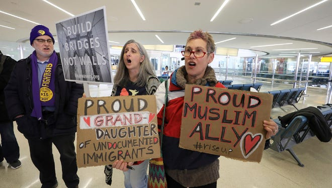 Kevin Brown of the Service Employees International Union, Kelly McDonald, of Montclair, and Jessica Sporn, of Montclair, chant in protest of the travel ban before the start of a press conference, Thursday, March 16, 2017, at Newark Airport, in Newark, N.J.