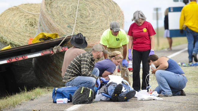 Emergency personnel work at the scene of a fatal head-on collision between two pickups on Highway 287, north of Wolf Creek, on Wednesday.