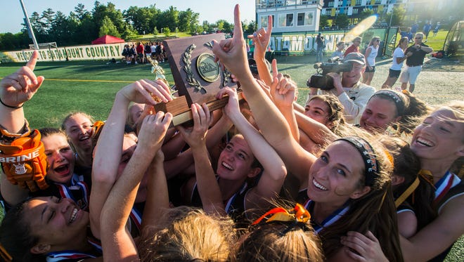 Middlebury celebrates with the trophy after their 13-10 win in the Division I girls lacrosse state championship game against CVU at Virtue Field at UVM on Friday night, June 8, 2018.