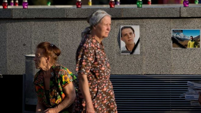 A woman is backdropped by pictures of victims of the MH17 air crash during a memorial concert in Kharkiv, Ukraine, Thursday, July 24, 2014. Two military aircraft carrying remains of victims from the Malaysian plane disaster departed for the Netherlands on July 24, while Australian and Dutch diplomats joined to promote a plan for a U.N. team to secure the crash scene which has been controlled by pro-Russian rebels.
