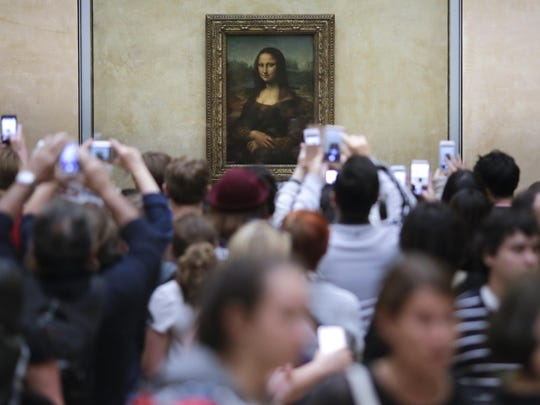 In this June 1, 2016, photo, visitors crowded in front of Leonardo da Vinci's painting 'Mona Lisa' at Musée du Louvre in Paris.