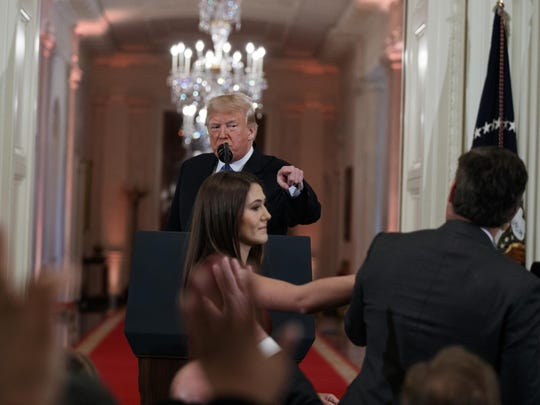 FILE - In this Nov. 7, 2018 file photo, President Donald Trump watches as a White House aide reaches to take away a microphone from CNN journalist Jim Acosta during a news conference in the East Room of the White House in Washington. CNN is suing the Trump administration, demanding that Acosta's press credentials to cover the White House be returned. The administration revoked them last week following President Trump's contentious news conference, where Acosta refused to give up a microphone when the president said he didn't want to hear anything more from him. (AP Photo/Evan Vucci, File)