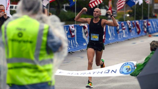 First half marathon finisher Danny Goodman crosses the finish line Sunday during the 11th annual Pensacola Marathon.