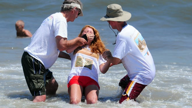 In this file photo, a surf baptism takes place with the help of Dick Sands, left, and Gary Steger of Son'Spot Ministries in Ocean City. Around 30 people were baptized, part of the seventeenth annual Jesus At The Beach Music & Ministry Festival.