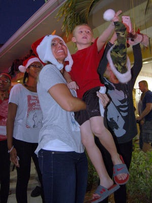 Cindy Hamilton and her son Hutch spot Santa as he arrives at the Shops of Marco.