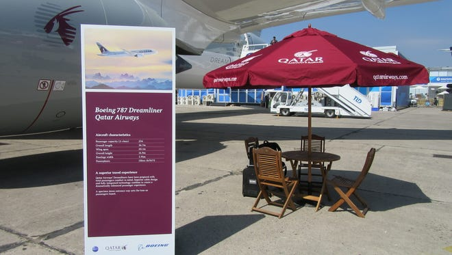 An information sign and a beach-style table and umbrella welcome visitors to a Qatar Airways Boeing 787 Dreamliner at the Paris Air Show on Wednesday, June 17, 2015.