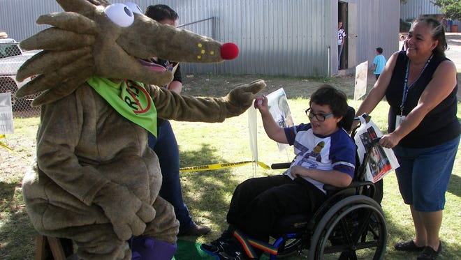 Doña Ana County Codes Enforcement and Animal Control mascot Carlos the Coyote greets a child at the recent Southern New Mexico State Fair in Las Cruces.