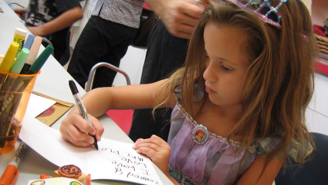 Kennedy Evans, 6, of Palm Desert, dressed as a fairy tale princess, writes on a greeting card at the Gilda's Club Desert Cities' Noogie Fest, the organization's yearly Halloween party.